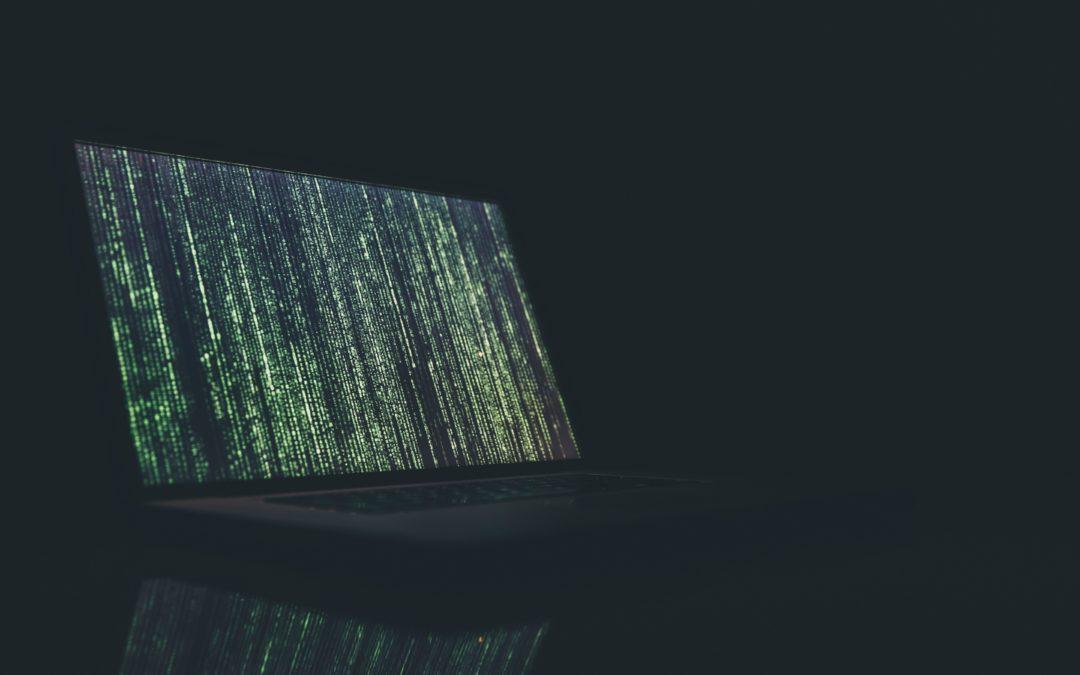 Laptop vor schwarzem Hintergrund zeigt Matrix-Code
